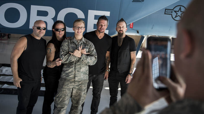 Members of the band Disturbed take a photo with an Airman during a tour of Nellis Air Force Base, Nevada, October 24.