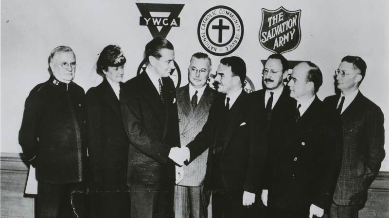 Leaders from the six founding organizations of the USO shake hands in 1941. USO photo