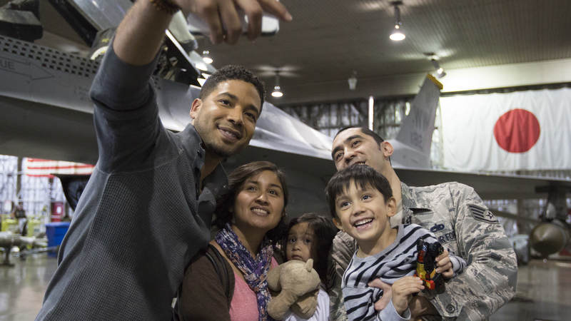"Jussie Smollett takes a selfie with a military family during the ""Empire"" USO tour to Japan."