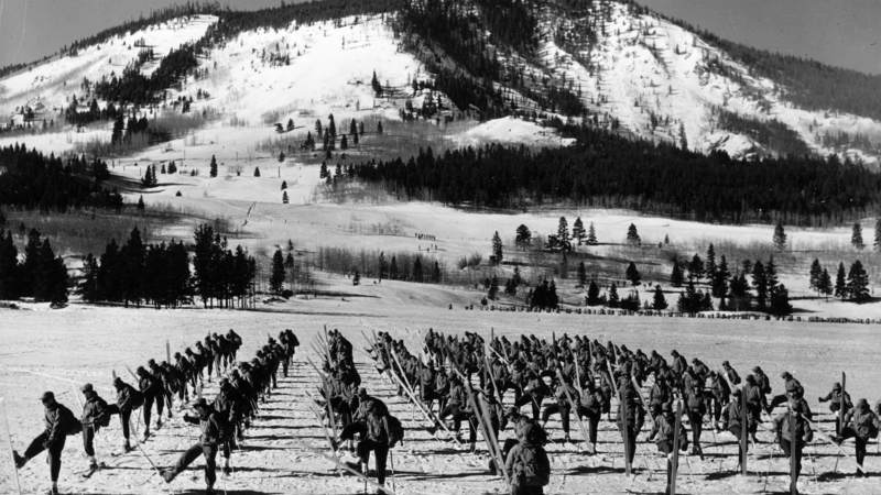 Approximately 100 soldiers from the 10th Mountain Division, 87th Mountain Infantry Regiment, Company L, execute an about face on skis under the command of Lieutenant William J. Bourke on a flat snow-covered field. In the background, smaller groups of skiers are visible training in the trees at the base of one of the mountains surrounding Camp Hale, Colorado.