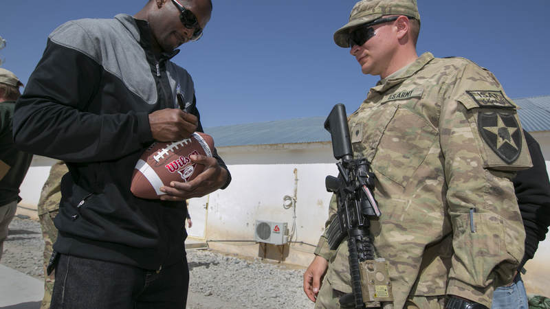Then-Denver Broncos cornerback Champ Bailey autographs a football for a soldier stationed in the Middle East during a stop on a weeklong USO/NFL tour in March 2013.