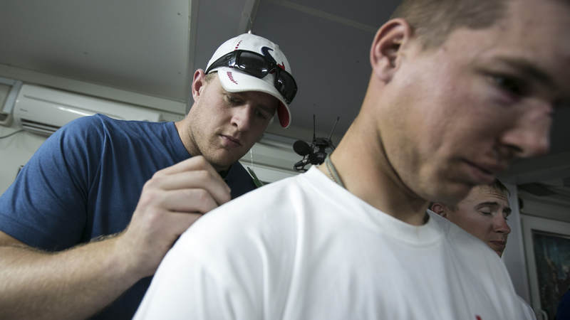 Houston Texans defensive end J.J. Watt autographs a shirt for an injured soldier stationed in the Middle East during a 2013 USO/NFL tour.