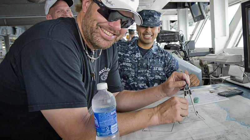 Musician Toby Keith flashes a smile as he takes a stab at understanding the navigation charts while touring the bridge of the aircraft carrier USS Abraham Lincoln.