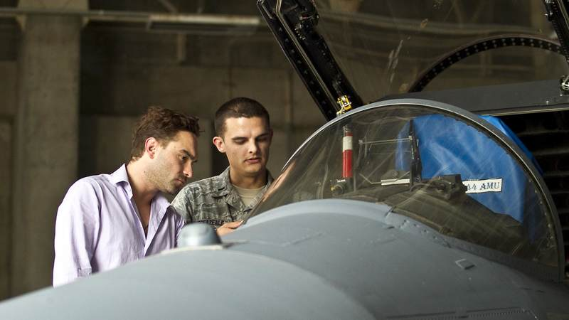 """The Big Bang Theory"" star Johnny Galecki gets a preview the cockpit of an F-15 aircraft by Air Force 1st Lt. Jason Breazeale during a 2012 USO tour to the Pacific."