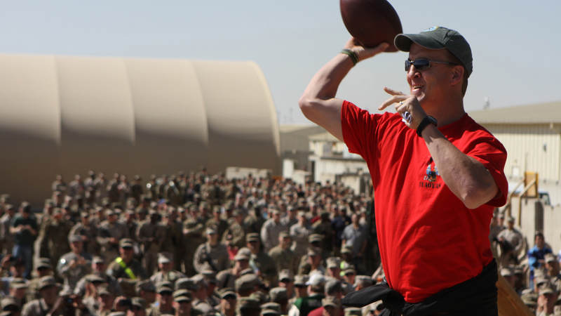 Peyton Manning tosses a pass into an audience of service members during 2013 trip to Camp Leatherneck, Afghanistan. Since teaming up in 1966, more than 180 NFL players, coaches, officials and executives have toured for the USO.