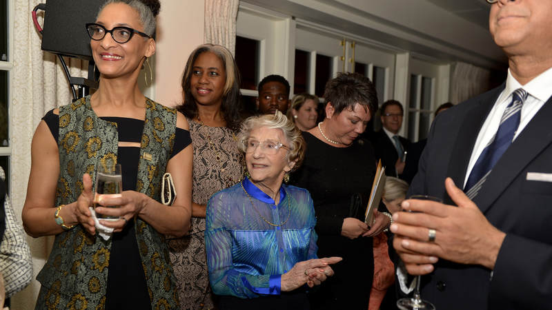 """Carla Hall, chef and co-host of ABC's """"The Chew,"""" and artist Lila Asher, also a WWII-era USO volunteer, listen to speeches."""