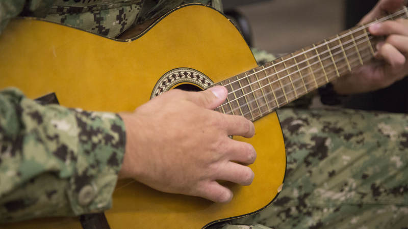A Navy Seabee strums an acoustic guitar Feb. 8 during a late-night layover at USO Ontario.