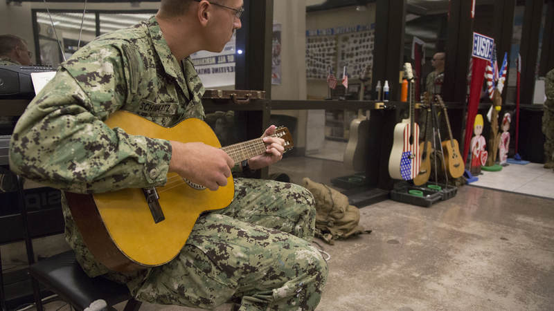 A Navy Seabee strums on an acoustic guitar Feb. 8 at 1:30 a.m. on a layover from Guam on his way home to Gulfport, Mississippi.