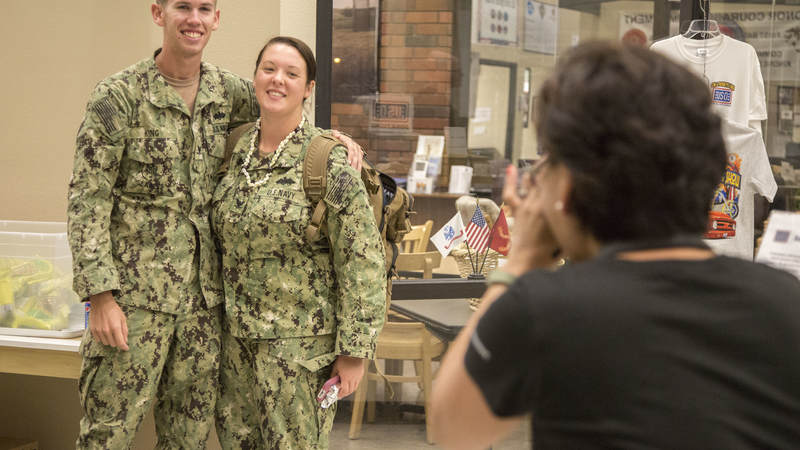 A Navy Seabee couple has their picture taken by USO volunteer Mariza Gatdula on Feb. 8 during a short layover at USO Ontario.
