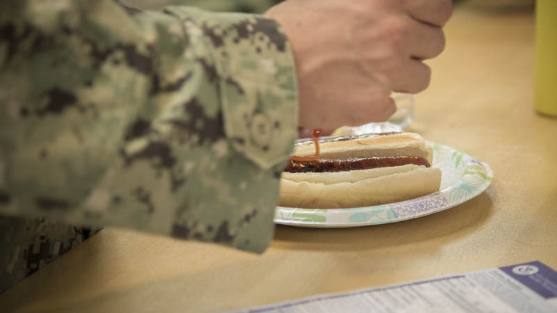 Navy Seabee fixes a freshly grilled hot dog Feb. 8 during a short, late-night layover at USO Ontario.