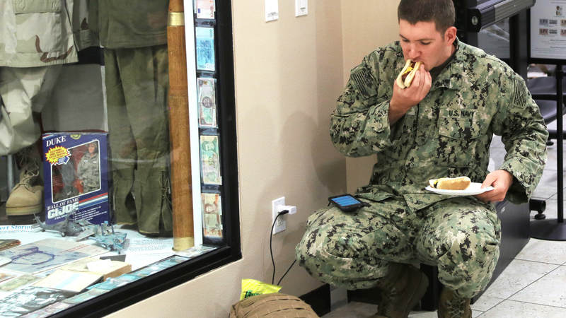 A Navy Seabee eats a hot dog and charges his phone Feb. 8 at USO Ontario during a short, late-night layover.