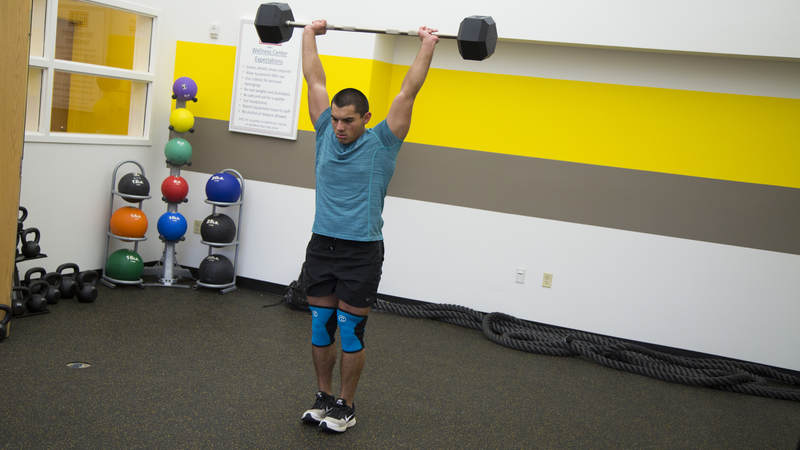 A service member lifts weights at the USO Alaska Wellness Center.