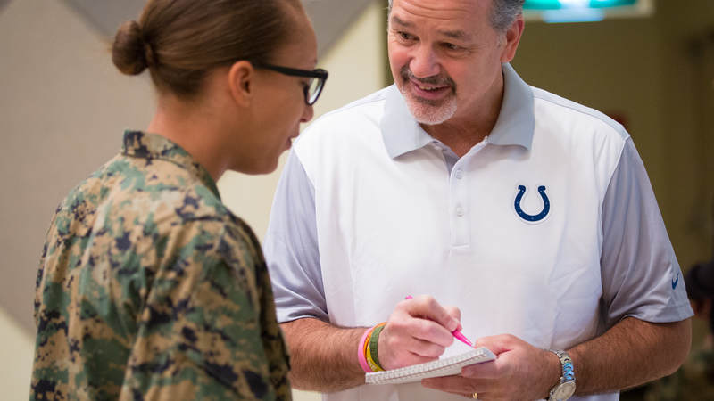 Indianapolis Colts head coach Chuck Pagano signs an autograph for a service member during a USO tour stop at Camp Foster in Okinawa, Japan, on Feb. 19.