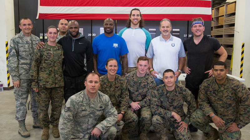 Coach Pagano along with players Pat McAfee (right), Anthony Castonzo (third right), D'Qwell Jackson (fourth rights) and Mike Adams (fourth left) pose for a photo with the Marine Corps K-9 Okinawa team during a USO tour stop at Kadena AFB in Okinawa, Japan, on Feb. 19.