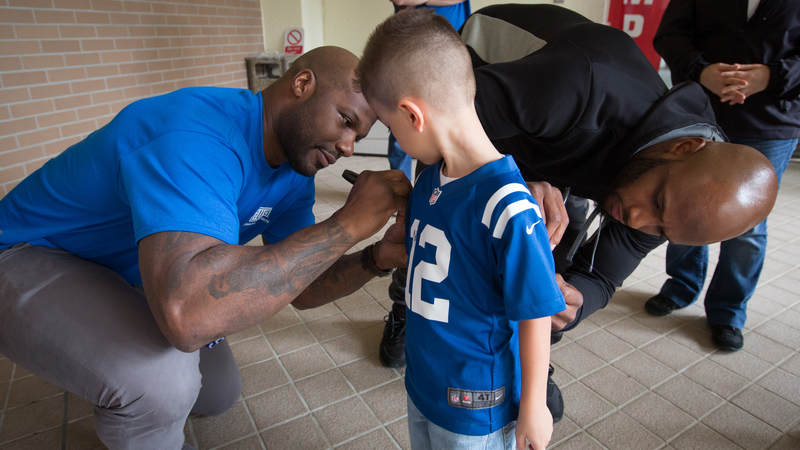 Jackson (left) and Adams (right) autograph the jersey of a young fan during a USO tour stop at MCAS Futenma in Okinawa, Japan, on Feb. 19.