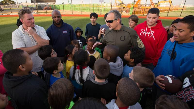 Coach Pagano (center), McAfee (left) and Adams (second left) encourage the children of service members after running them through football drills at a USO tour stop at a kids' after-school athletics program at Fleet Activities Yokosuka naval base on Feb. 17.