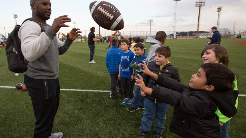 Jackson (left) tosses a football with the children of service members during a USO tour stop at a kids' after-school athletics program at Fleet Activities Yokosuka naval base on Feb. 17.