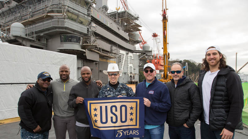 Jackson (second left), Adams (third left), McAfee (third right), Anthony Castonzo (right) and Coach Pagano (second right) pose for a photo with service members on the flight deck of the USS Ronald Reagan at Fleet Activities Yokosuka naval base on Feb. 18.
