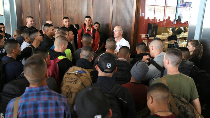 Marines gather around USO of North Carolina volunteer JC Cunningham for a briefing after deplaning March 9 at Raleigh-Durham International Airport.