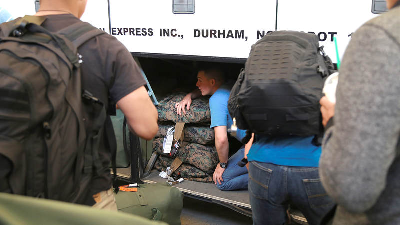 A Marine helps his fellow service members pack their gear March 9 inside a bus headed for Camp Lejeune, North Carolina. The group of Marines spent the afternoon at the USO inside Raleigh-Durham International Airport.